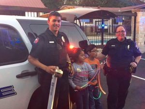 Officers smiling by vehicle and next to children.